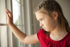parental alienation: sad girl looking out the window