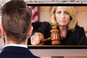 image of an attorney watching a computer monitor where a judge is ruling