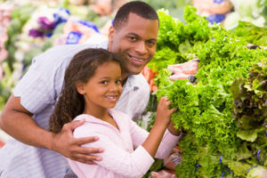 black father and daughter buying lettuce in a supermarket