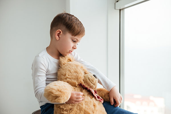 Psychological domestic violence/child abuse: sad boy holds his teddy bear for comfort